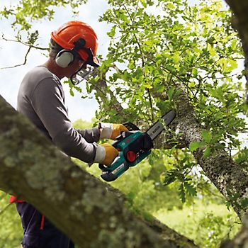man using chainsaw to saw branches off of a tree