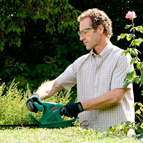 man holding hedge trimmer with two hands