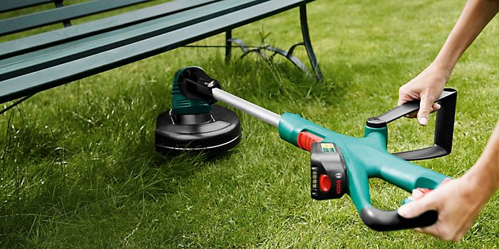 Woman using grass trimmer