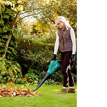 Woman using the Bosch ALS 30 Corded Garden Blower & Vacuum to blow garden leaves from the lawn
