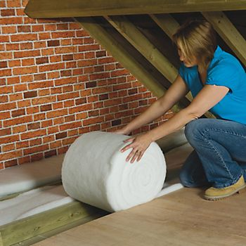 Woman fitting loft insulation