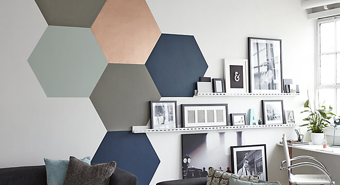 """hexagons of different colour and finish paints on a wall in a room"""