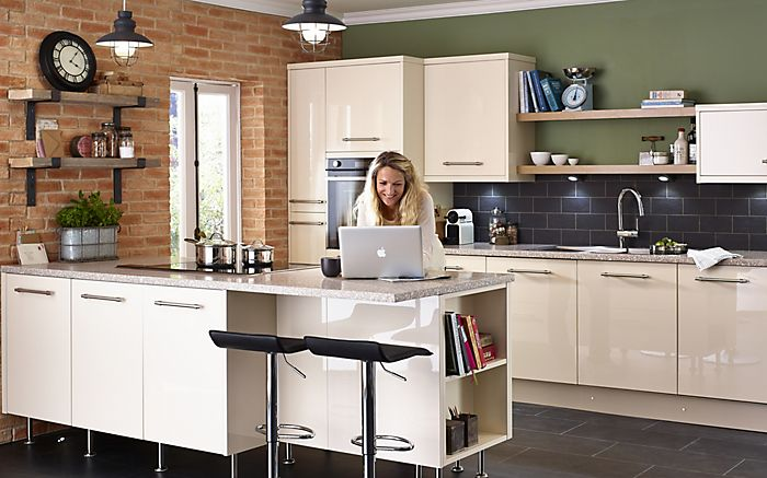 Woman on laptop in Cooke & Lewis Raffello High Gloss Cream Slab Fitted Kitchen