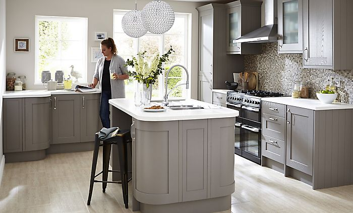 """Woman reading magazine in Cooke & Lewis Carisbrooke Taupe fitted kitchen"""
