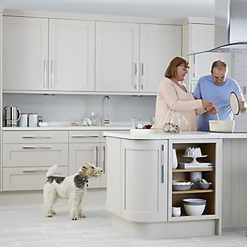 Couple cooking in Cooke & Lewis Carisbrooke Cashmere flat panel Shaker fitted kitchen