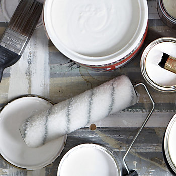 cans of paint on a floor with brushes and rollers