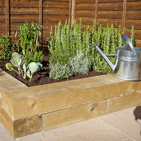 herbs in planter with watering can