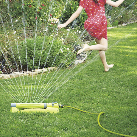 Child playing in sprinkler in the garden