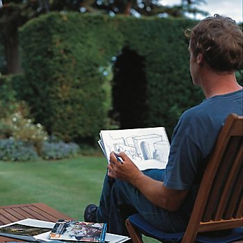 Man sat in garden drawing garden design plan