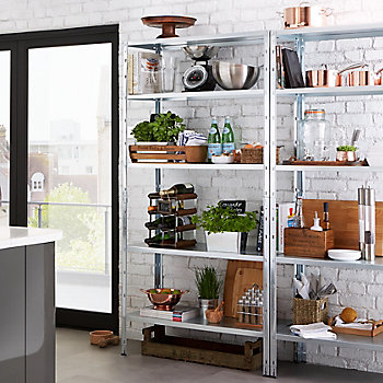 Open shelving unit filled with utensils, kilner jars and other kitchen items