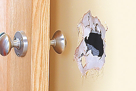 picture of hole in wall caused by door handle