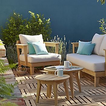 wooden garden furniture on decking against a blue wall in a garden