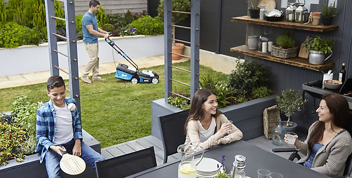 """man mowing lawn with Mac Allister lawnmower while family chat and play"""