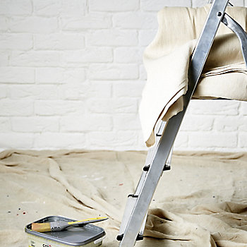 Ladder in front of a brick wall painted white