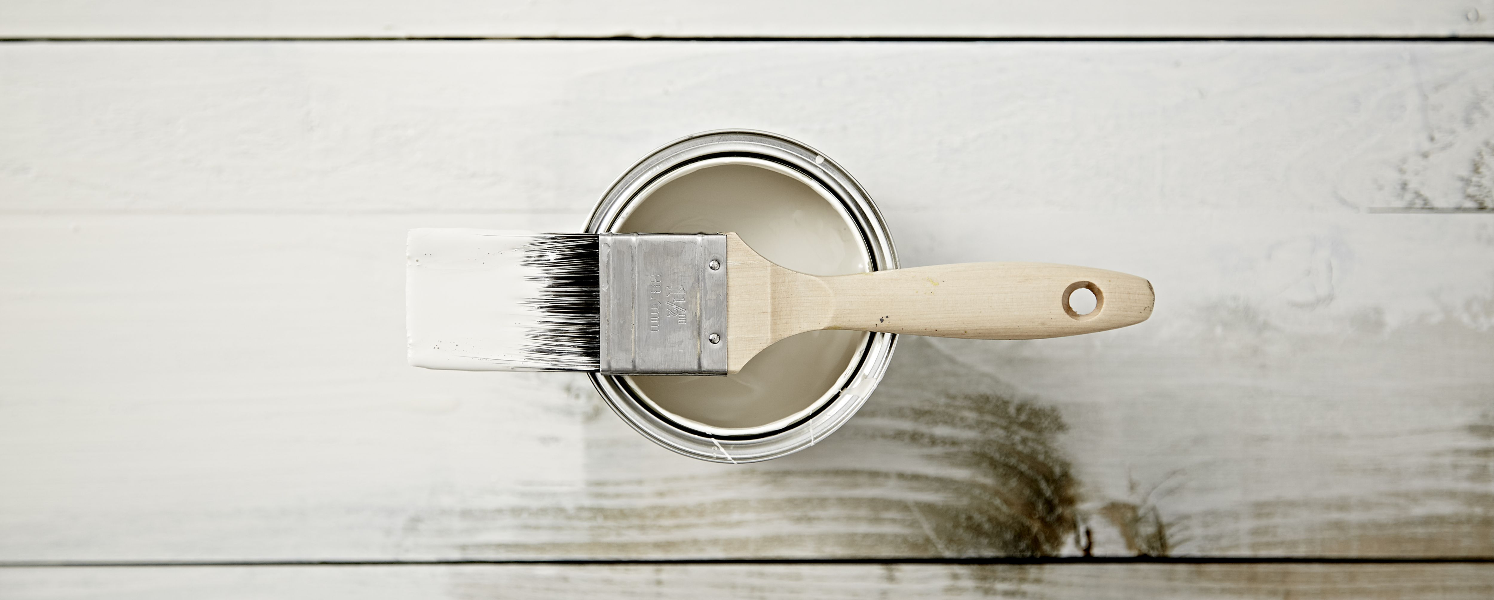 """""""A selection of grey paint in tins and some paint brushes"""""""