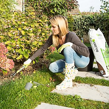 woman tidying her flower bed with hand fork