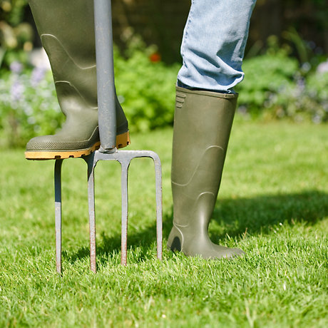 person in wellies using garden fork
