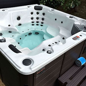 couple in a hot tub with headrests and drinks holders set