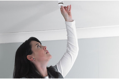 Woman testing smoke alarm