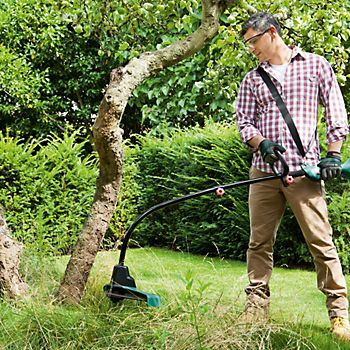 Man using the Bosch Art 35 electric corded brush cutter
