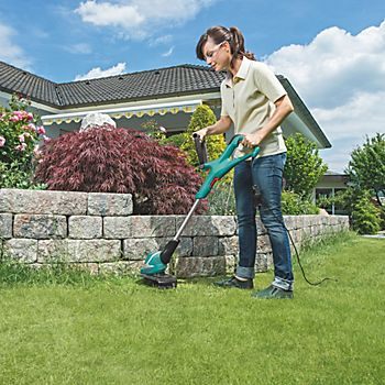 Woman using Bosch Art 30 electric corded grass trimmer