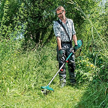 Man wearing protective goggles and gloves while using grass trimmer