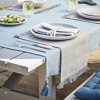 Table dressed with rural picnicware including tablecloth and placemats