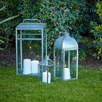 Cluster of three Blooma galvanised glass & steel lanterns on grass in garden