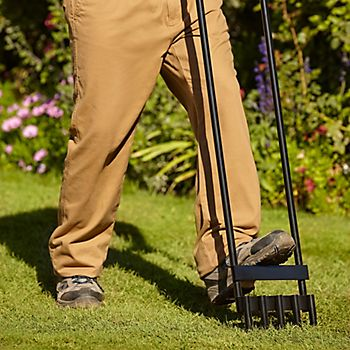 Man aerating lawn with the Verve hollow tine aerator