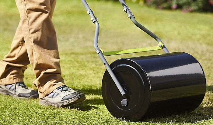 """Man rolling lawn with the Verve Pack and Flatten Lawn Roller"""