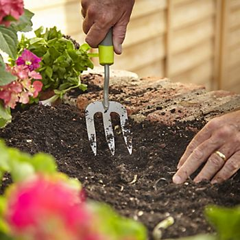 Gardener using a Verve fork to ready the soil to plant bedding plants