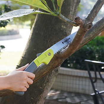 Person chopping a branch from a tree using the Verve Steel Folding Saw