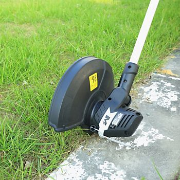 Mac Allister 430W grass trimmer with it's head rotated to trim edge of grass alongside a garden path
