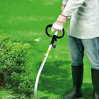 Person using a B&Q 25CC petrol brushcutter with D handle