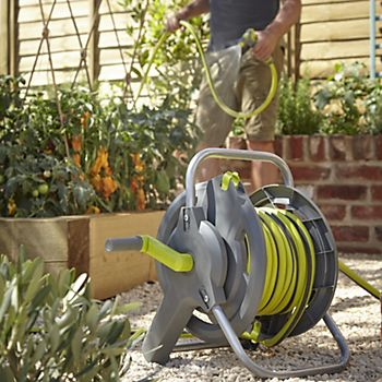Man using the Verve Wall Mounted Hose Reel to water plants in the garden