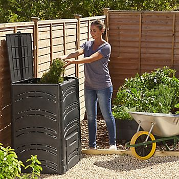Woman filling composter with garden debris from metal wheelbarrow
