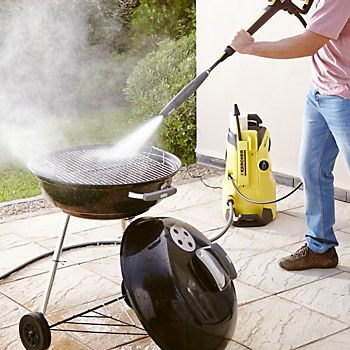 Karcher K4 Premium Full Control Home Pressure Washer cleaning a barbecue