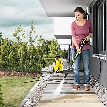 Woman cleaning patio with Karcher K4 Pressure Washer