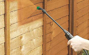 spraying paint onto a fence
