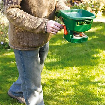 Man using Evergreen Cut & Feed Lawn Spreader