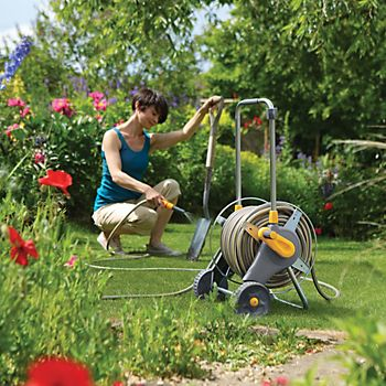 Woman using the Hozelock Wheeled Hose Cart to wash a garden spade