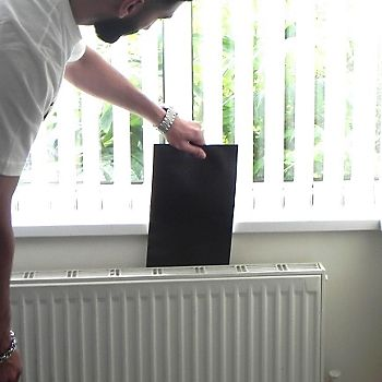 man putting a radiator foil behind a radiator