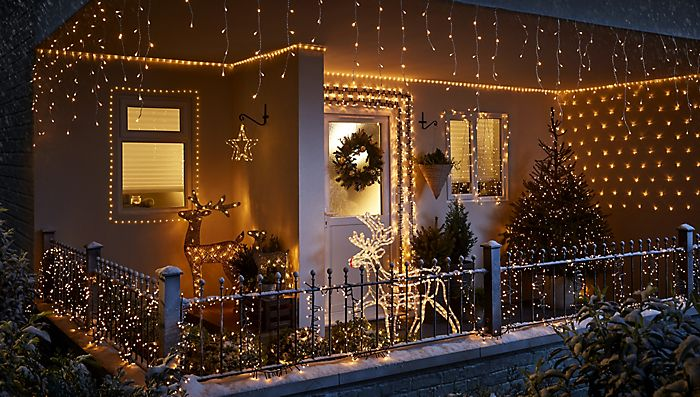 Front garden decorated in warm white Christmas lights