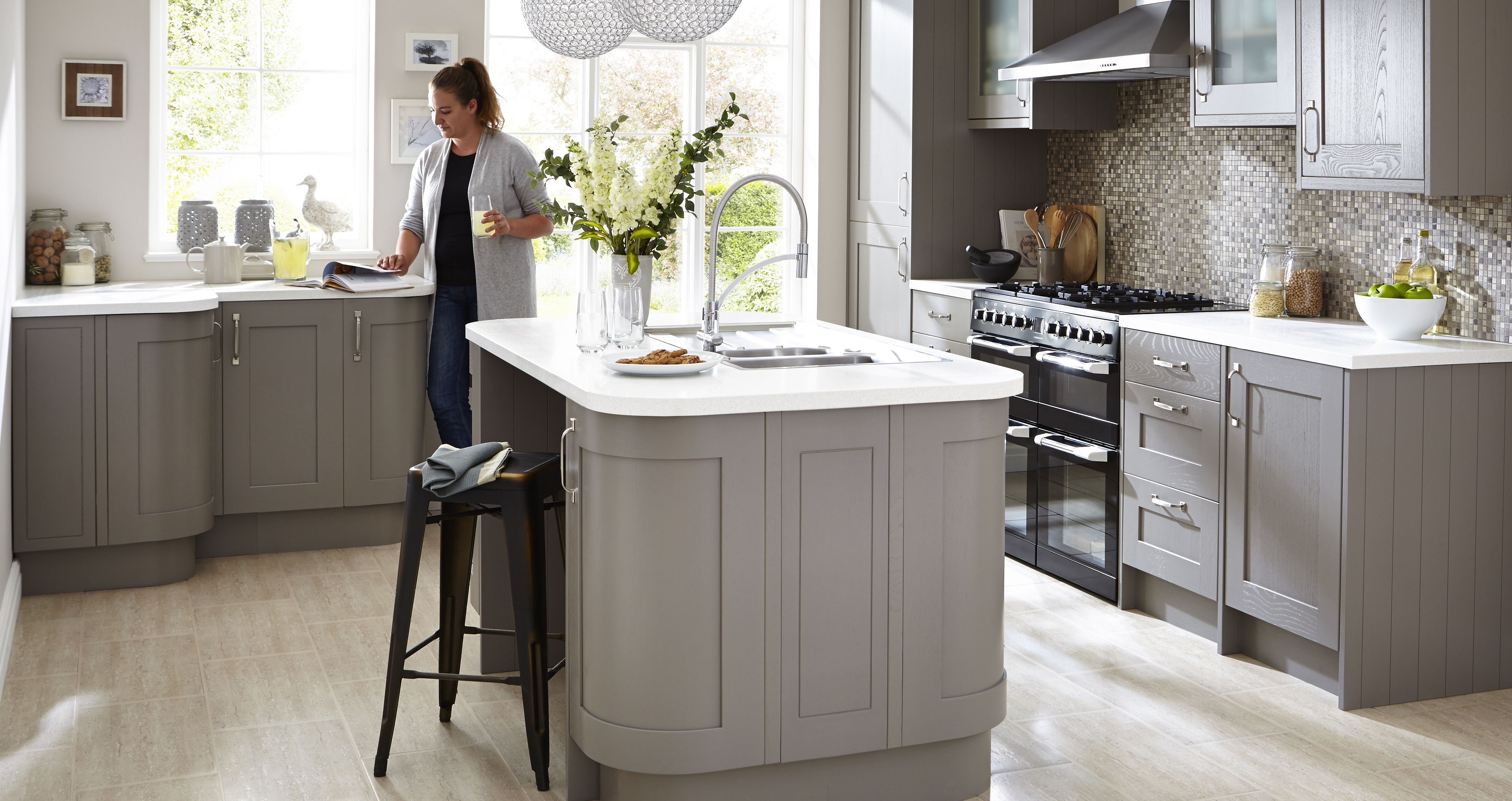 Woman reading magazine in cooke lewis carisbrooke taupe fitted kitchen