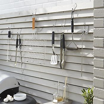 Barbecue cooking utensils hanging on wall hooks