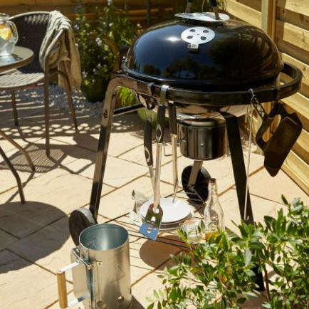 Charcoal barbecue with utensils including chimney starter