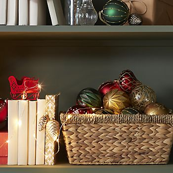 Traditional Christmas tree baubles in a basket on a shelf