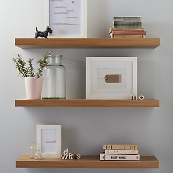 Floating wood effect shelves with picture frame and plants on