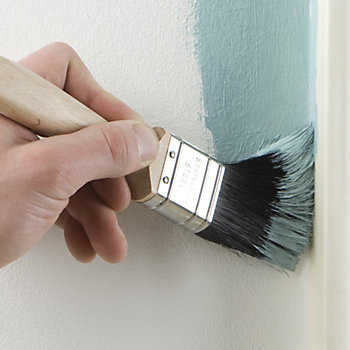 painting a wall with a brush