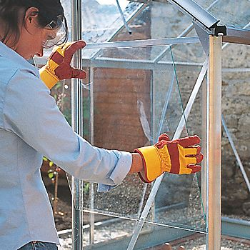 Woman fitting new glazing to greenhouse